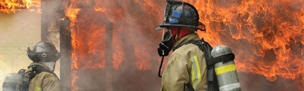 Firefighter walking in front of a structure fire