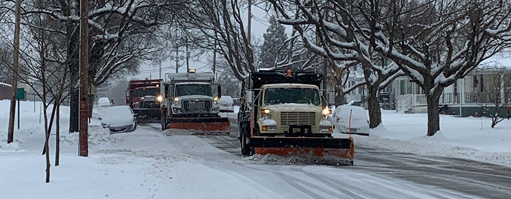 Snow plows riding down a city street