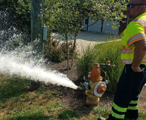 Public Services crew member watching water flow from hydrant